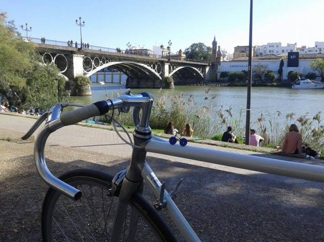 a veloboton and companion relaxing by the Puente de Triana in Sevilla, Spain